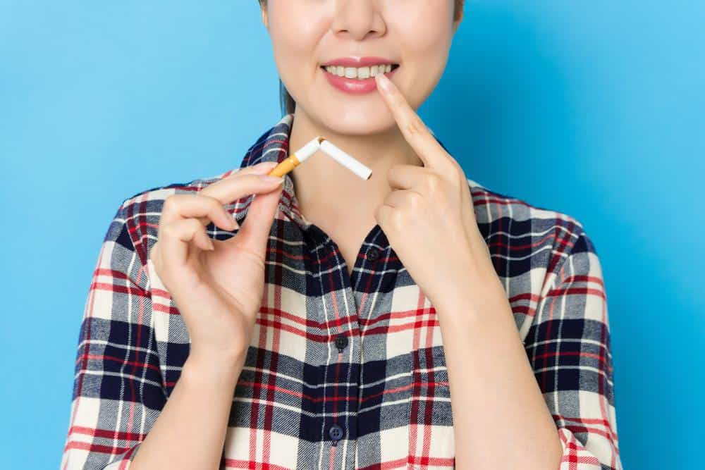 woman holding broken cigarette because it can cause oral cancer